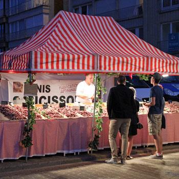Marktkraam met klanten op avondmarkt